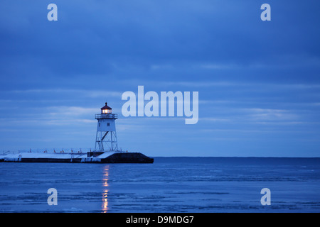 Grand Marais, Minnesota breakwater lighthouse beacon on a winter morning. - Stock Image