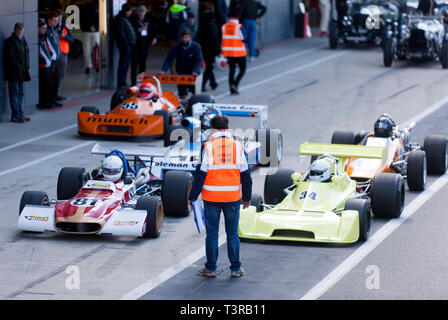 Several Historic Formula 2 Race cars assemble in the International Pit Lane, for a parade lap, during the 2019 Silverstone Classic Media Day/ Test Day - Stock Image