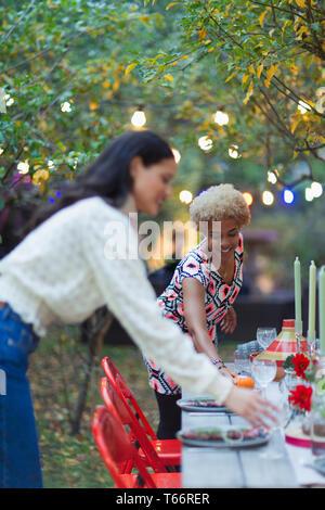 Women friends setting table for dinner garden party - Stock Image