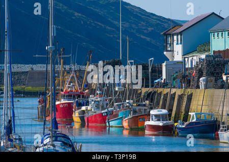 Aberystwyth Wales, UK. 11th Apr, 2019. UK Weather: Local inshore fishing boats lined up in a rainbow of colours against the harbour wall on a gloriously bright and sunny morning in Aberystwyth on the Cardigan Bay coast of west Wales.