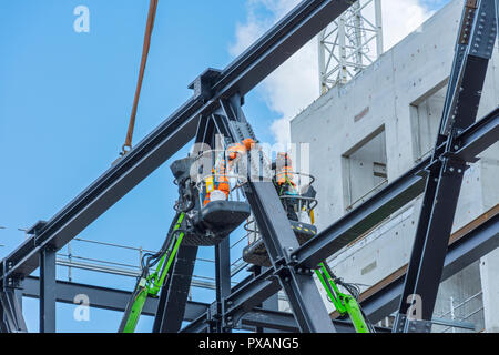 Workmen on aerial platforms erecting steelwork for the Manchester University Engineering Campus building, Booth Street East, Manchester, England, UK - Stock Image
