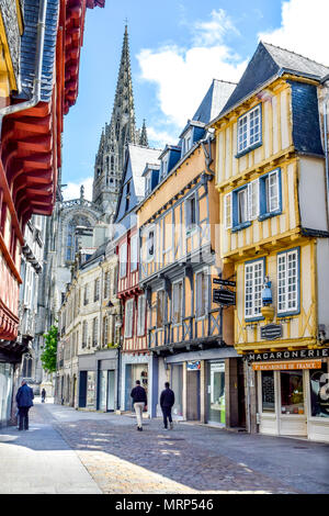 Pastel half-timbered buildings and a cathedral jutting into the sky are amongst the sights on a quiet Sunday stroll in Quimper, Brittany, France. - Stock Image