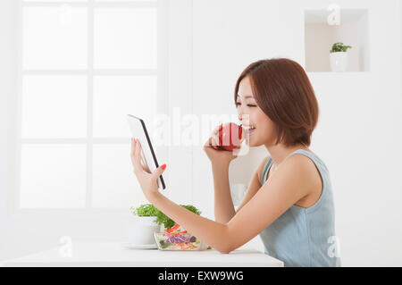 Young woman holding an apple and using touch pad, - Stock Image
