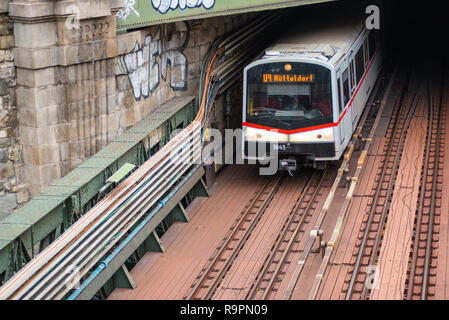 Metro U-Bahn train comes out of a tunnel and goes under Zollamtssteg Bridge while crossing the river in Vienna, Austria. - Stock Image