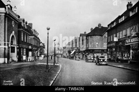 Station Road, Beaconsfield, Buckinghamshire, looking towards the station, with the Saracen Library and Bookshop on the left, and W H Smith and other shops on the right.      Date: circa 1930s - Stock Image