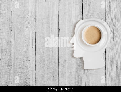 Coffee cup on plate in human head form - Stock Image