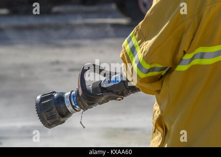 Firefighter holding a nozzle on a fire hose. - Stock Image