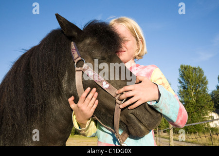 Young girl hugging a black pony. - Stock Image
