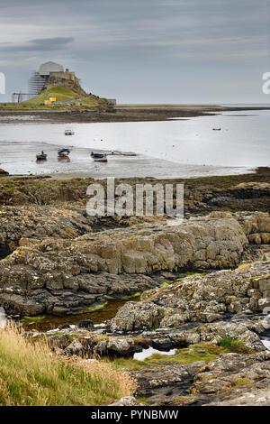 Lindisfarne Castle with scaffolding from Steel End of Holy Island with fishing boats at low tide Berwick-upon-Tweed England UK - Stock Image