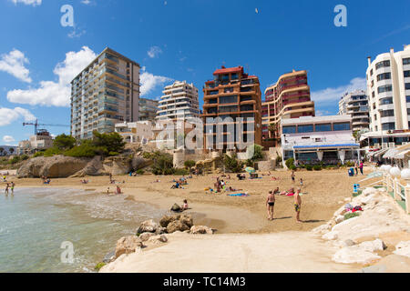 Calp Spain view of Playa Cantal Roig beach waves and seafront hotels and apartments on the Spanish Mediterranean coast - Stock Image