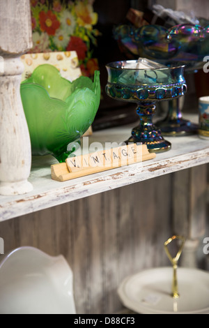 Shelf in antique shop with antique and vintage bowls. Word 'vintage' in front of them created from wooden - Stock Image