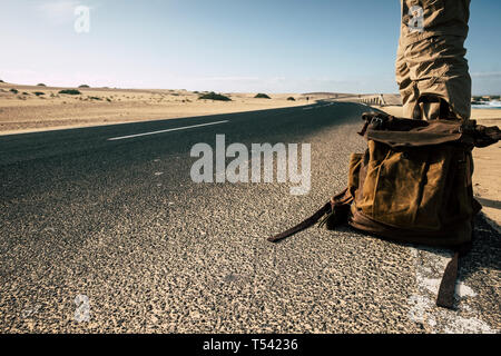 Close up ground point of view of man with leather backpack travel and wait for a car to share the trip together - sand and desert dunes and black asph - Stock Image