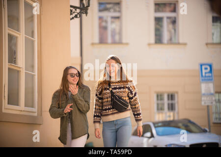 Two young smiling women walking on the streets. Mid shot - Stock Image