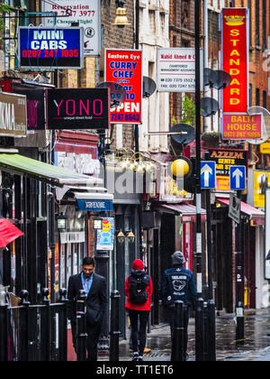 Brick Lane shops and restaurants - Brick Lane is a vibrant restaurant, nightclub and shopping street in the Shoreditch area of East London. - Stock Image