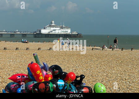 Eastbourne Pier and Beach with colourful balloons in foreground, Eastbourne, East Sussex, England, UK - Stock Image