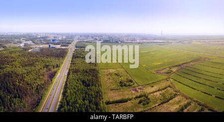 Long straight highway entered from the countryside to the large city. Panoramic aerial view. Saint Petersburg, Russia - Stock Image
