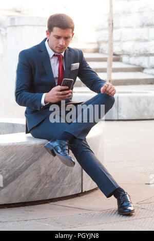 Young handsome businessman in a suit and tie lookink at the smartphone sitting on a marble bench in the park - Stock Image