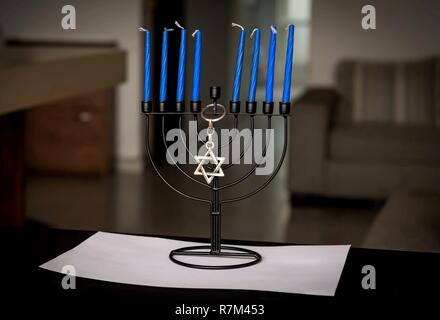 Traditional Jewish Chanukah Menorah candelabrum with eight blue candles and a Star of David key chain on a table, Jewish holiday Hanukah concept image - Stock Image
