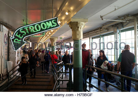 Busy scene and a restroom direction sign at Pike Place Market, Seattle, Washington State, north west USA. - Stock Image