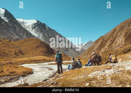 Big group of hikers having rest against mountains and river. Space for text - Stock Image