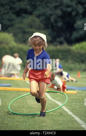 primary schoolgirl in obstacle race at school sports day - Stock Image
