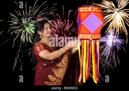 An Indian woman looking at the traditional Diwali lantern during Diwali festival in India, on the backdrop of Diwali fireworks. - Stock Image