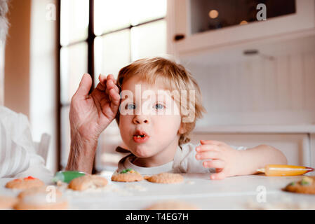 A midsection of senior grandmother with small toddler boy making and decorating cakes at home. - Stock Image