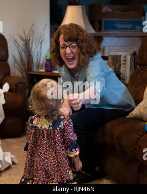 Adult Caucasian woman laughs and reaches out toward female child toddler. - Stock Image