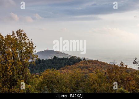 Beautiful view of Assisi town (Umbria) in autumn from an unusual place, behind an hill with orange, yellow and green trees. - Stock Image