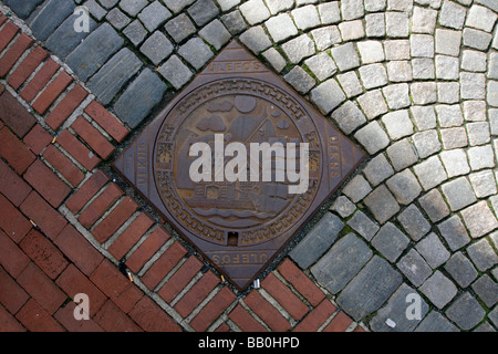 Decorated Drainage grate in the pavement of the Bryggen in Bergen, Norway - Stock Image