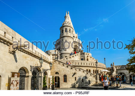 Tourists enjoy a sunny day at Fisherman's Bastion, part of the Buda Castle Complex in Budapest Hungary. - Stock Image