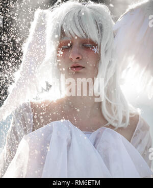 Portrait of beautiful blonde girl in image of good angel with wings dressed in white clothing against background of snowfall. - Stock Image