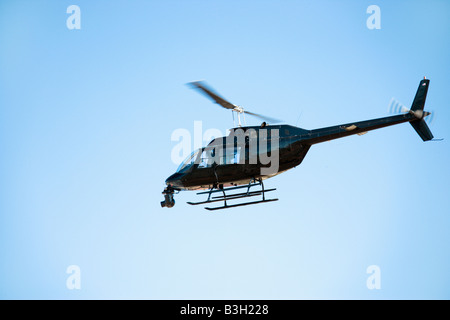 Low angle shot of helicopter flying through blue sky - Stock Image