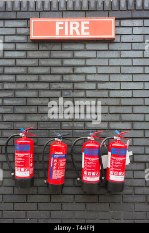 A row of four wall-mounted red Chubb portable dry powder fire extinguishers set against a grey brick wall - Stock Image