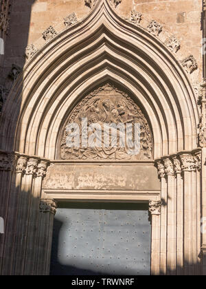 The Door of piety. Cathedral Of The Holy Cross And Saint Eulalia, with an ogee arch flanked by high pinnacles carved with great finesse. In Barcelona, - Stock Image