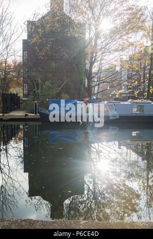 Reflection of Old building, tree and Barge with piercing sun as the sunsets in Regents Canal Hackney, London, England. - Stock Image