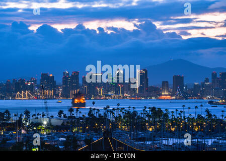 Calm sunrise, pre-dawn, over the San Diego skyline, with North San Diego Bay and docked sailboats off Shelter Island, California, USA - Stock Image