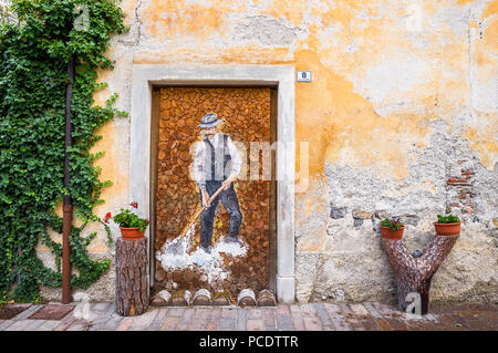 Painting of a Italian farmer painted onto a wood store in a external doorway. - Stock Image