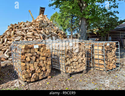 Piled cut & split 'Oak' firewood, open-end bins with pricetag,  firewood operation & sales yard. - Stock Image