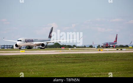 A Qatar Airways Airbus A350, and a Jet2 Boeing 737, preparing for take off from Manchester Airport, England. - Stock Image