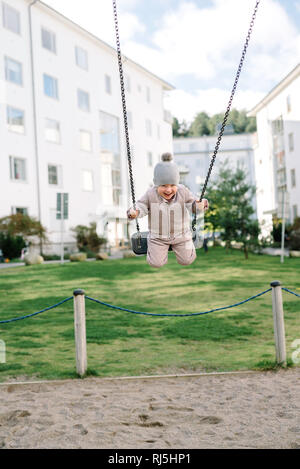 Boy having fun on swing in playground - Stock Image