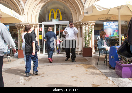Large man using mobile phone outside burger bar with other customers - Stock Image