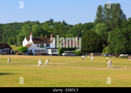 Local teams playing a cricket match on village green in front of Barley Mow pub on a summer's evening. Tilford Surrey England UK - Stock Image