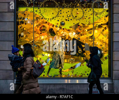 Edinburgh, Scotland, United Kingdom, 8th November 2018. Christmas celebrations: A busy Saturday in the capital city centre. Shoppers walk past the colourful Christmas decoration window display at Harvey Nichols department store - Stock Image