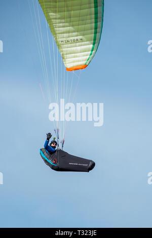 Man paragliding over Hunstanton cliffs on North Norfolk coast, East Anglia, England, UK. - Stock Image