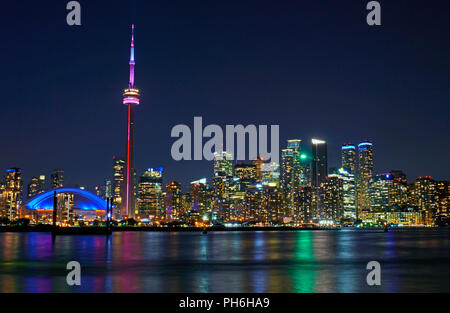 Toronto evening skyline including downtown landmark buildings CN Tower, Roger's Centre and office skyscrapers in financial district and waterfront - Stock Image