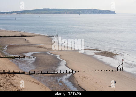 Early morning walkers on Shanklin beach, Isle of Wight with Culver Down in the background - Stock Image