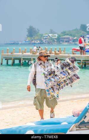 Local vendor sells cheap sunglasses many knockoffs of famous brands ob West Bay Beach Roatan Honduras. - Stock Image