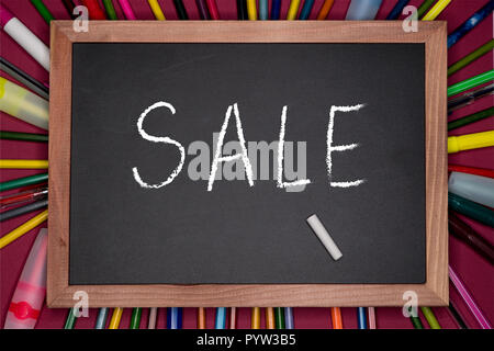 SALE written on chalkboard with wooden frame on purple background with stationery - Stock Image