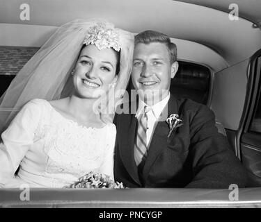 1960s SMILING HAPPY JUST MARRIED BRIDE AND GROOM SITTING IN BACK SEAT OF LIMOUSINE TOGETHER LOOKING AT CAMERA  - b22782 HAR001 HARS FUTURE NOSTALGIA OLD FASHION AUTO SEAT STYLE VEHICLE PLEASED JOY LIFESTYLE CELEBRATION FEMALES MARRIED SPOUSE HUSBANDS LUXURY HALF-LENGTH LADIES PERSONS AUTOMOBILE MALES JUST CONFIDENCE TRANSPORTATION B&W EYE CONTACT DREAMS HAPPINESS HEAD AND SHOULDERS CHEERFUL FORMAL DRESS ADVENTURE AND AUTOS EXCITEMENT IN OF SMILES CONNECTION AUTOMOBILES JOYFUL STYLISH VEHICLES MORNING DRESS MID-ADULT MID-ADULT MAN TOGETHERNESS WIVES YOUNG ADULT WOMAN BLACK AND WHITE - Stock Image